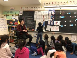 Jimmy Yu overseeing a young boy write his answers on a chalkboard before a class of young children