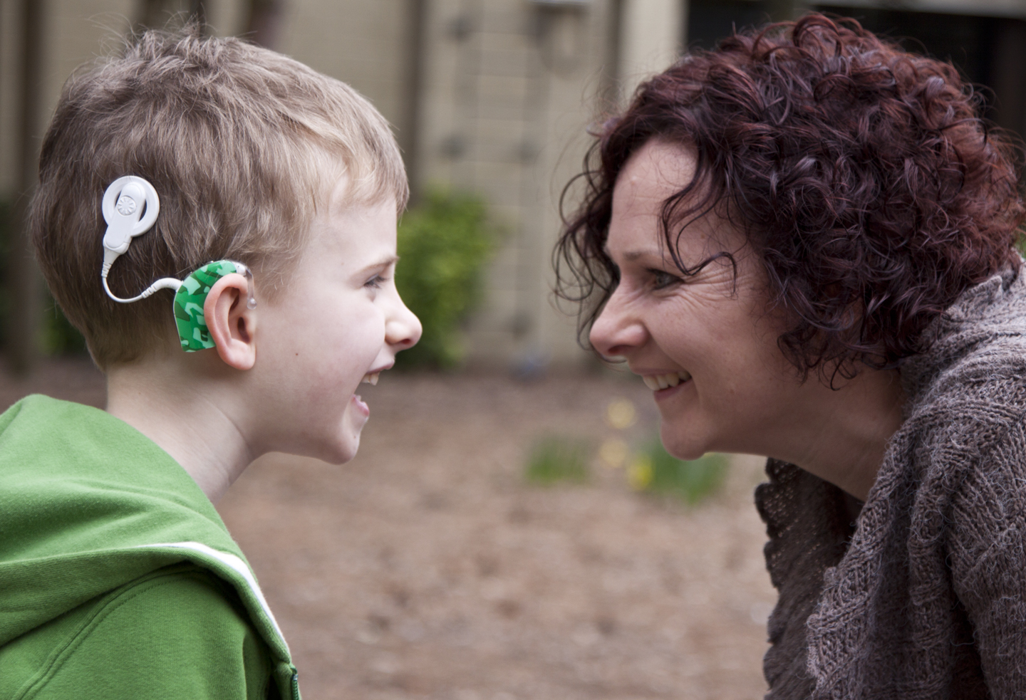 Son with hearing aid and mother