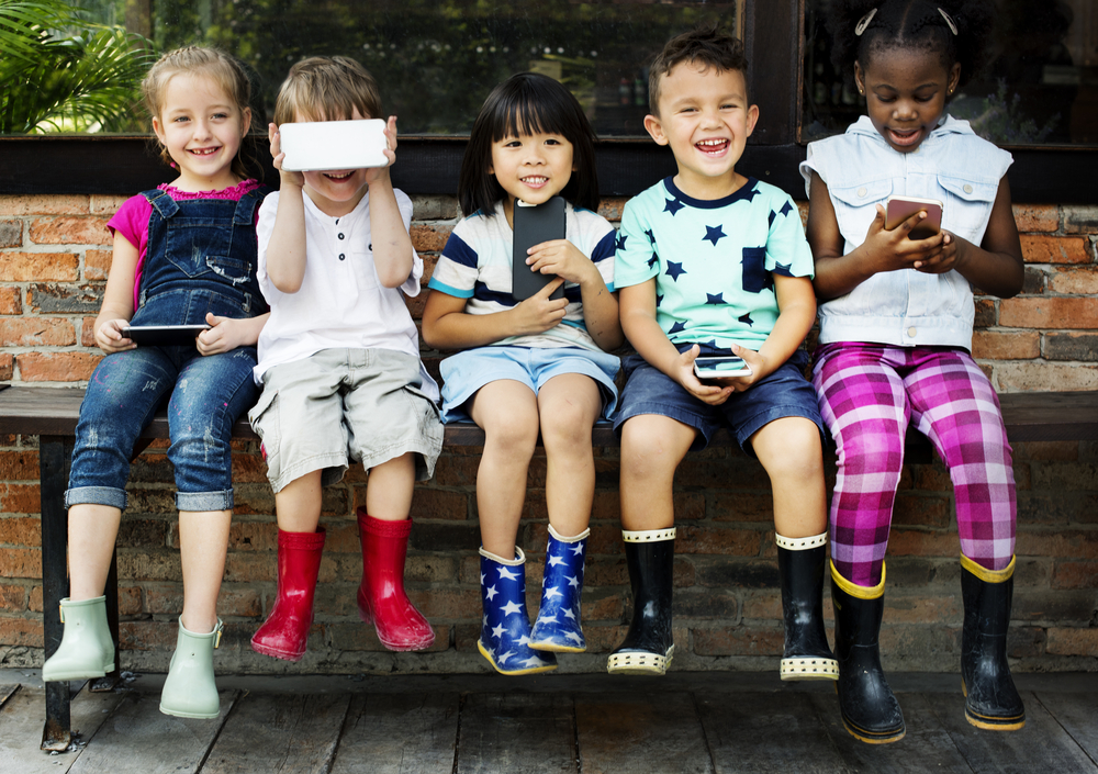 Group of kids sitting with cell phones