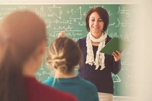 A teacher instructing students in front of the blackboard.